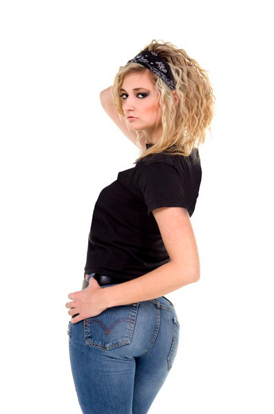 Casual young woman in jeans and a black t-shirt looks back over her shoulder