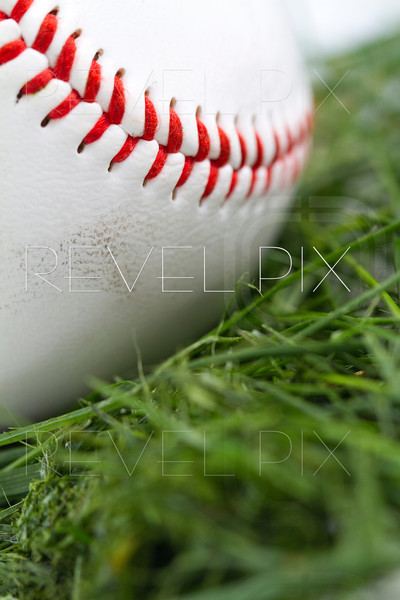 Angled macro shot of smudged baseball in grass.