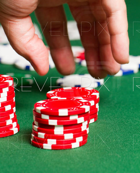a close up as a hand moves in to grab some red poker chips on a poker table.