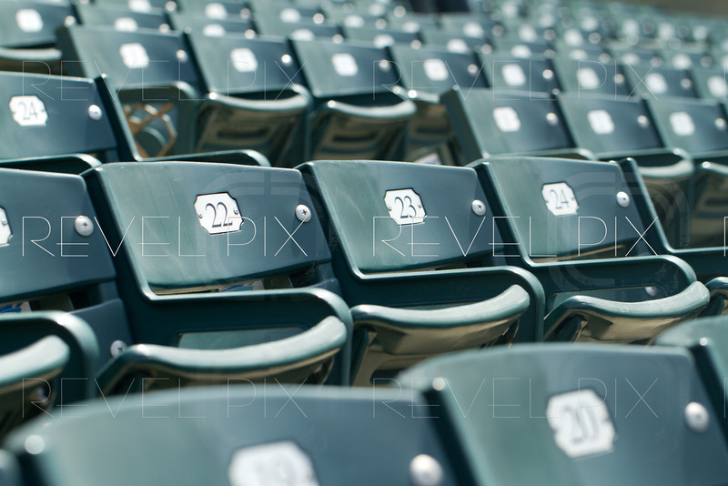 a generic angled shot of empty stadium seating. shallow depth of field. Numbers are seen on seats.