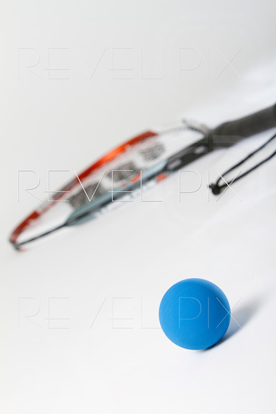 racquetball racquet blurred in distance with ball in foreground