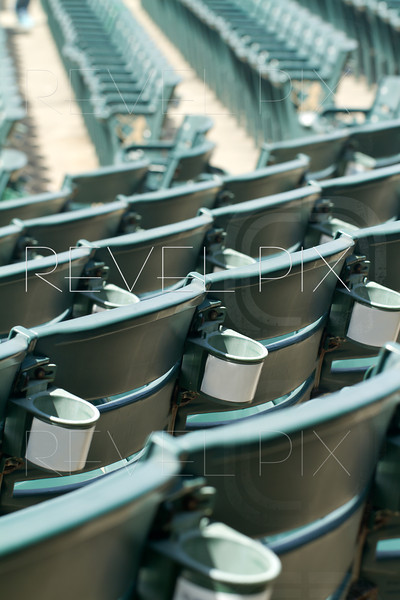 a generic shot of empty stadium seating with cup holders from behind with another section seen in the distance. shallow depth of field.