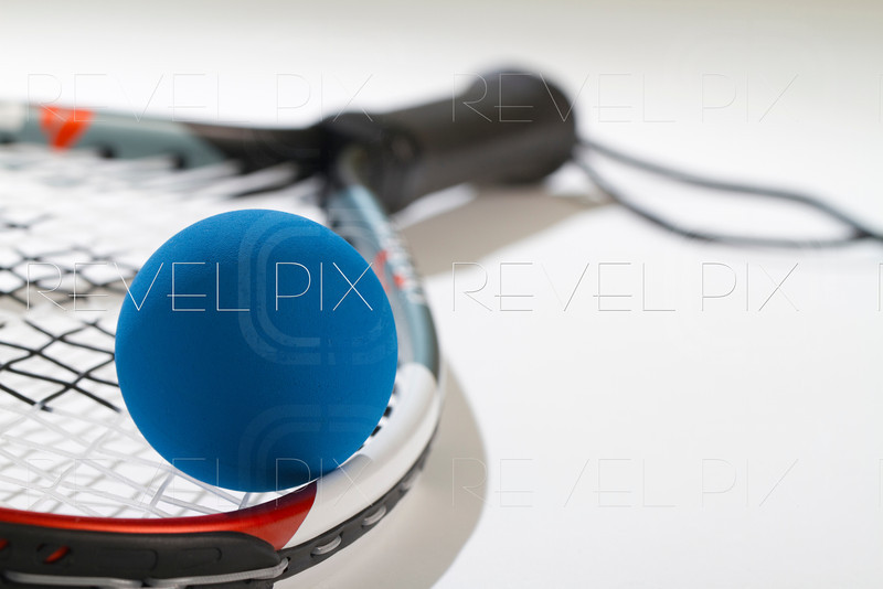 blue racquetball in foreground laying on racquet strings. Handle is blurred.