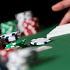 a macro side angle shot of poker gambling chips in stacks with hand on cards. shallow depth of field. close up