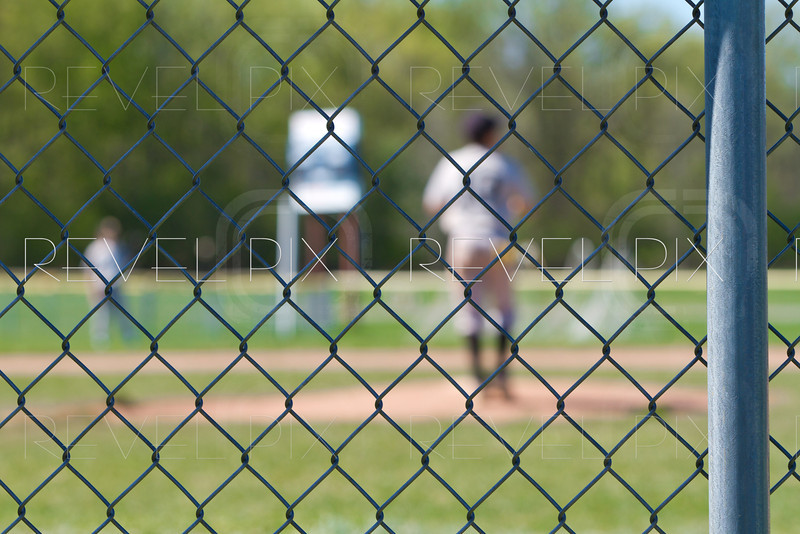 a chain link baseball fence with a blurred out backdrop of a baseball game going on.