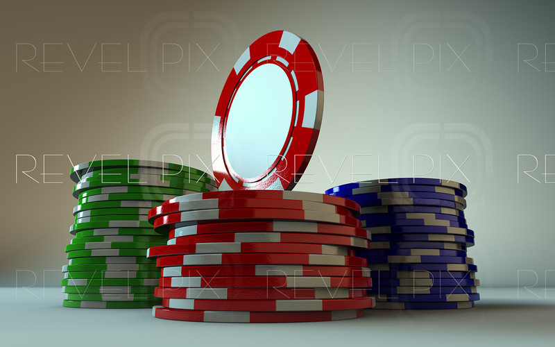 a low angle macro shot of 3 stacks of gambling chips. A red one is standing on the red stack facing the left.
