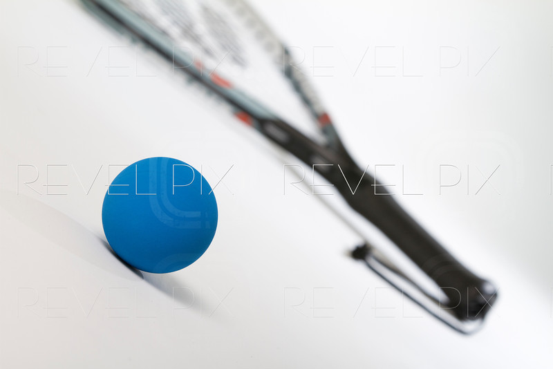 blue racquetball ball in foreground with raquet handle and wrist loop in background blurred. shot on white