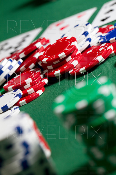 vertical shot looking over a stack of gambling chips into the pot in the middle. shallow depth of field