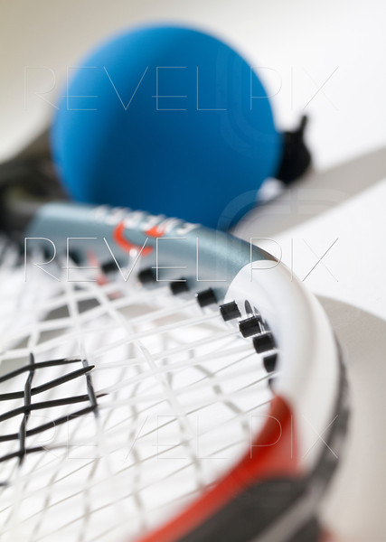 Blue racquetball blurred near handle. Part of strings and racquet are in focus. View from head of racquet.
