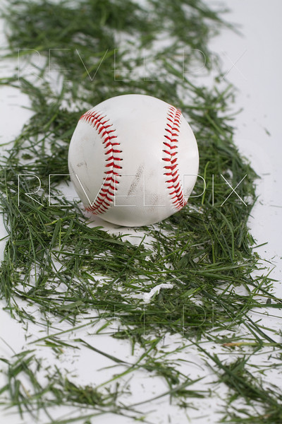 a worn baseball laying on blades of grass on white.