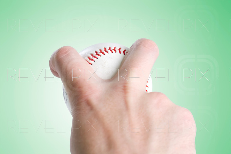 split finger baseball grip on green gradient background. with clipping path to place your own background. focus is on ball and fingers.