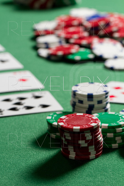 a vertical shot of poker chips from a players point of view. chips are out of focus in middle pot.