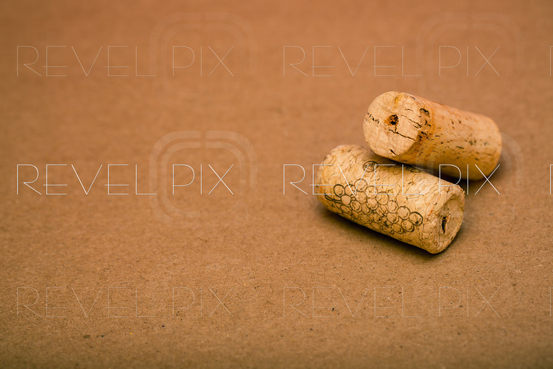 two wine corks stacked against a brown textured background. macro with copyspace