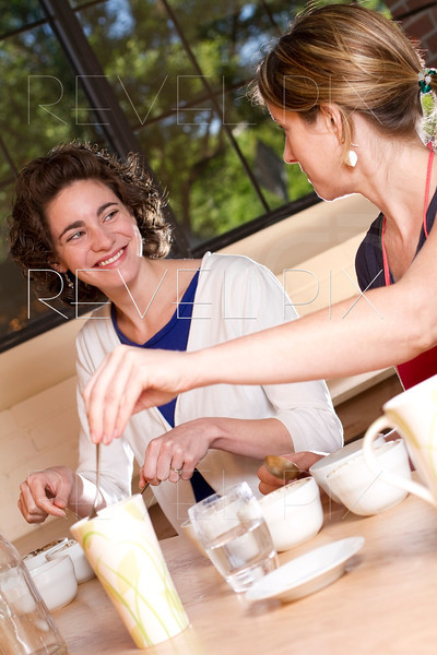 two women taste and compare brewed coffees at a cafe. Process is known as Coffee Cupping.