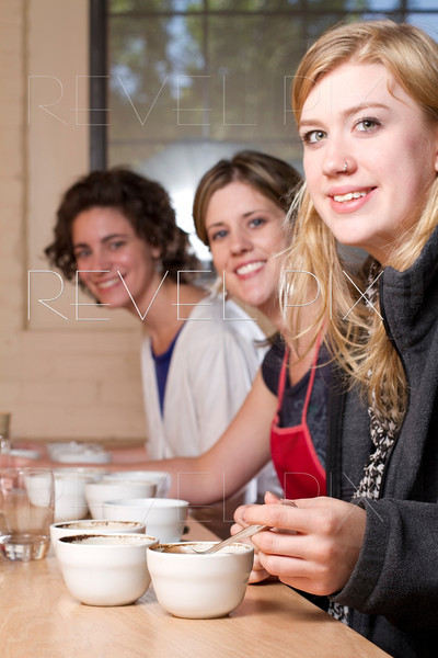 three women smile at camera during a taste and compare of brewed coffees at a cafe. Process is known as Coffee Cupping.