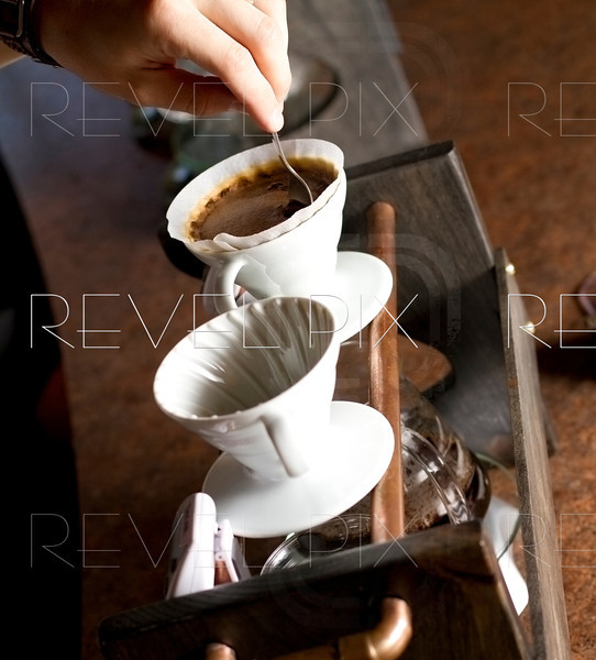 an employee stirs filtering water of a single cup of coffee. water filters down through to glass mugs underneath