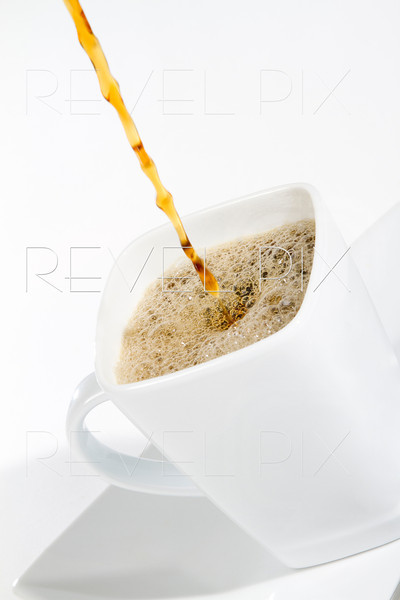 a stream of coffee pouring into a white coffee mug. shot on white