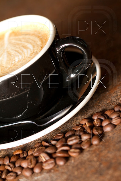 a freshly brewed Cappuccino with coffee beans surrounding the cup