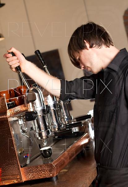 a barista brews an espresso working in a cafe.