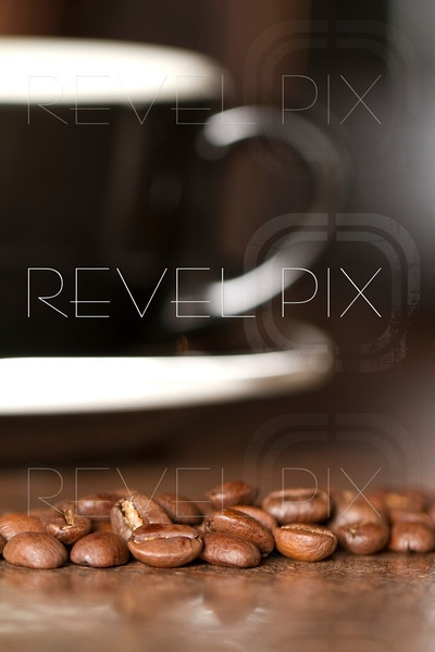 Macro shot of some roasted coffee beans with a coffee mug in the background out of focus.