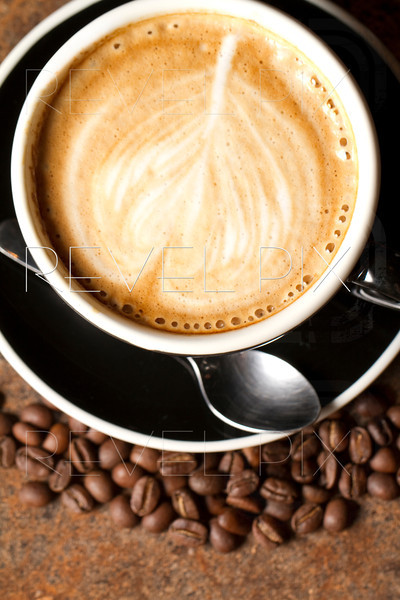 an above macro shot of a Cappuccino with coffee beans surrounding the cup.