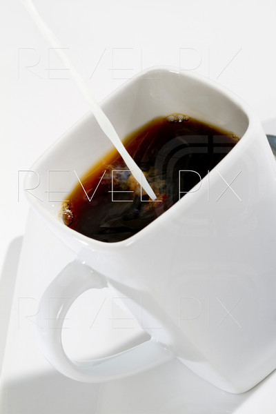 creamer poured into black coffee. angled shot on white.