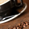 Macro shot of a pile of coffee beans in front of a Cappuccino. focus on beans