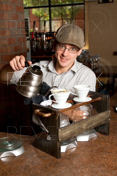 a barista smiles at the camera while brewing a special cup of coffee.