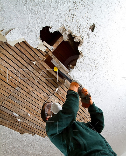 vertical shot from below of a man pulling down plaster ceiling lathe with a crowbar. large hole in ceiling.