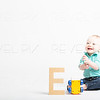 Baby Smiling on White with Wooden Letter and Toy