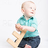 Baby Holding Wooden Letter E Looking Off Camera
