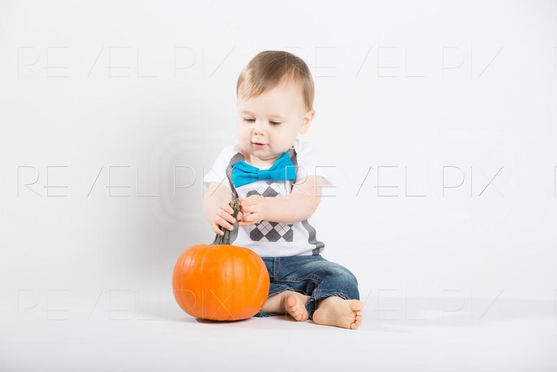 Baby Sits Grabbing Stem of Pumpkin