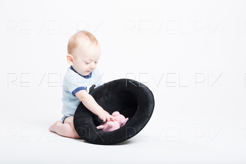Baby Reaching into a Black Hat for Stuffed Animal