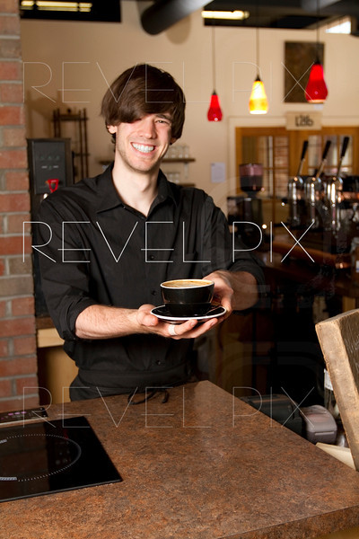 a barista hands you your cappuccino, focus is on cappuccino.