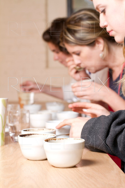 three women taste and compare brewed coffees at a cafe. Process is known as Coffee Cupping. focus is on coffee crusted cups.