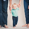 Baby Holding Parents Hands Staring Into Camera