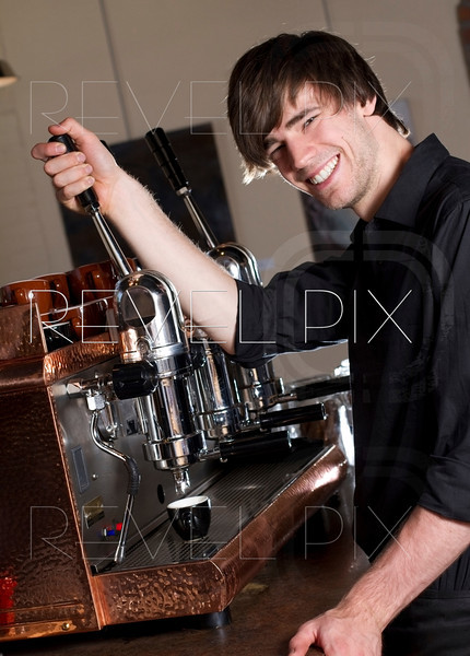 a barista smiles at the camera while brewing an espresso working in a cafe.
