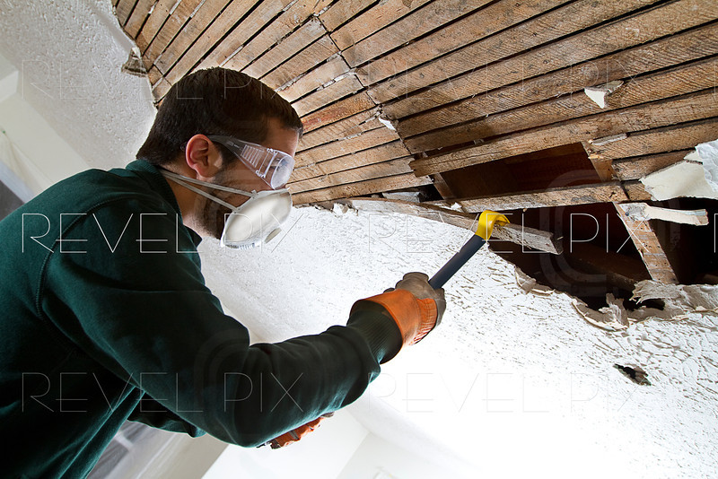 man removing plaster lathe from ceiling with a crowbar