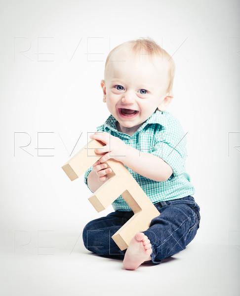 Baby Holding Wooden Letter E Smiling