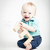 Baby Holding Wooden Letter E Smiling
