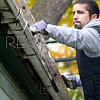 a man is on a ladder cleaning out the dirty gutter. shallow depth of field. focus on hand in gutter.