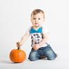 Baby Holds Pumpkin Stem Kneeling