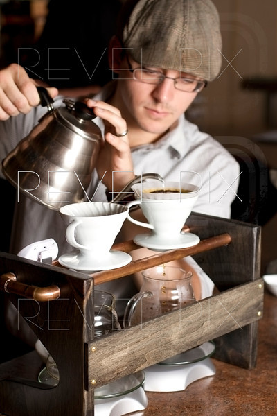a barista brews a single cup of coffee using a unique method and traditional style. the hot water drips through the filter and grinded beans above into glass mugs. focus on contraption