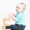 Baby Looking Over Shoulder with Wooden Letter E