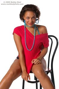 Beautiful womanin red sweater and short, shorts with blue beads and earrings