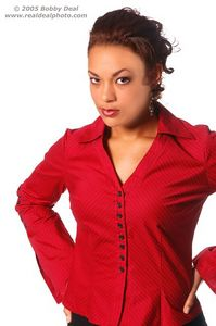 Beautiful woman in red pin stripe blouse and black slacks showing a bit of annoyance