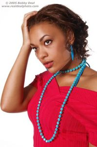 Beautiful woman in red sweater and  blue beads and earrings