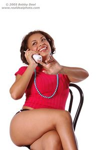 Beautiful woman in red talking on a cordless telephone and jesturing to hang on a second,