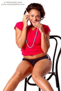 Beautiful woman in red talking on a cordless telephone,