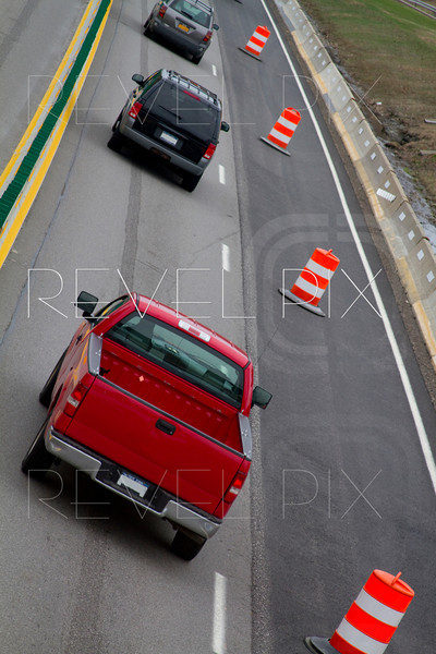 Vehicles travel in a row of single lane because barrels block off right side for paving construction